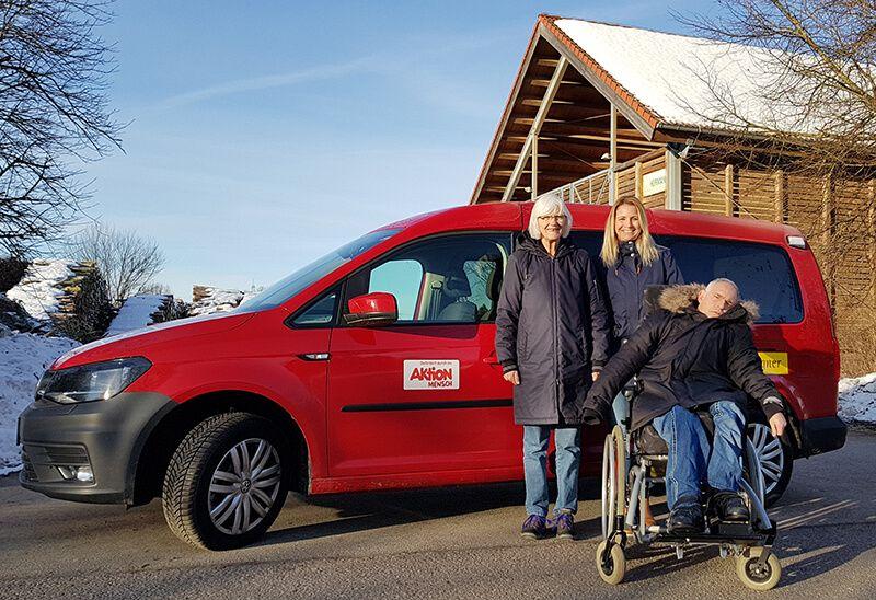 Gesamtleiterin Simone Kögl (Mitte) mit zwei der potenziellen Fahrgäste vor dem neuen VW Caddy