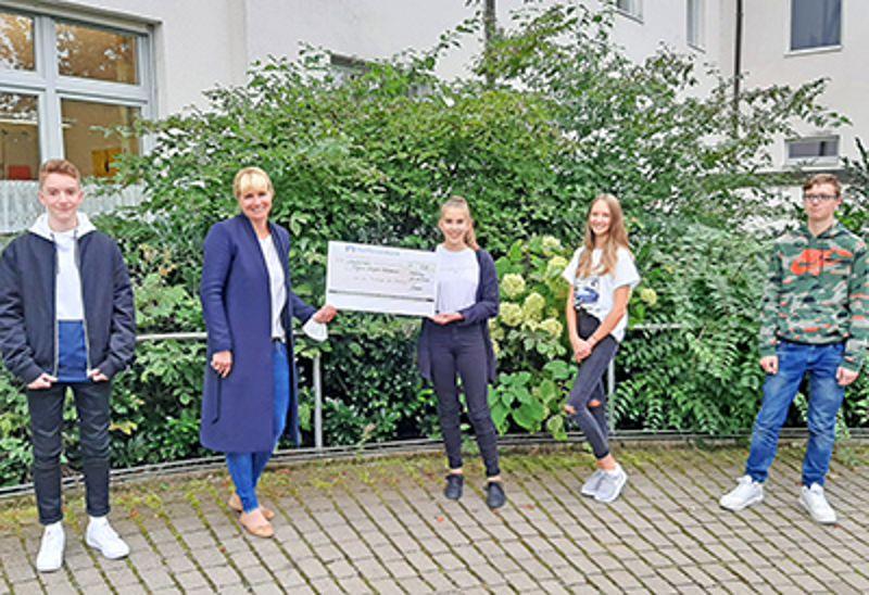 Die vier Jugendlichen bei der Übergabe des Spendenschecks an Simone Kögl als Vertreterin von Regens Wagner Holzhausen